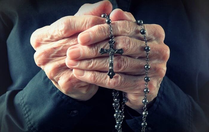 Older person holding a cross necklace