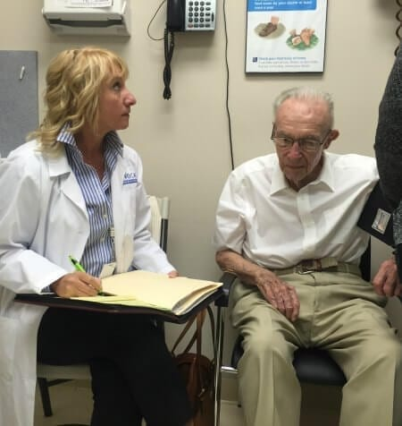 A doctor taking notes on an elderly patient