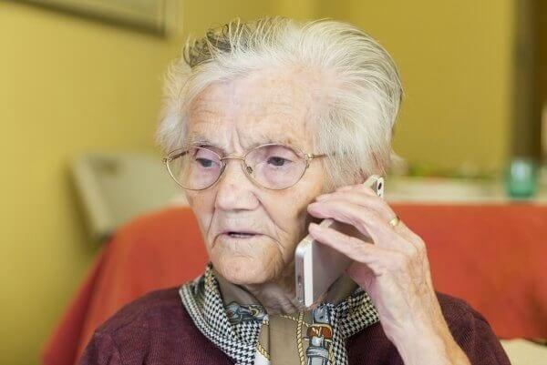 An elderly woman talking on the phone