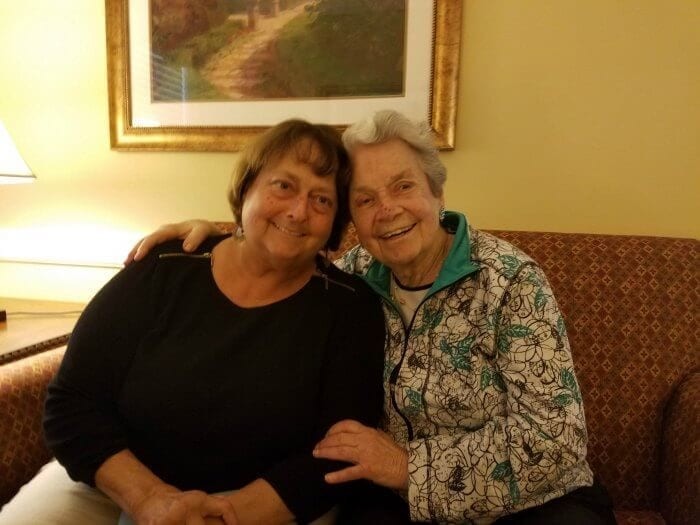 Two woman smiling together on a couch