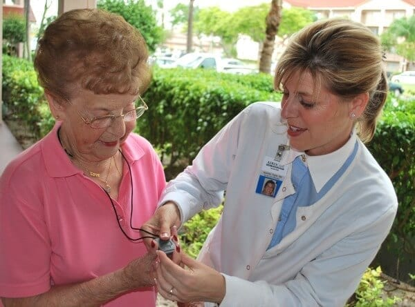 A doctor demonstrating a medical alert system to patient