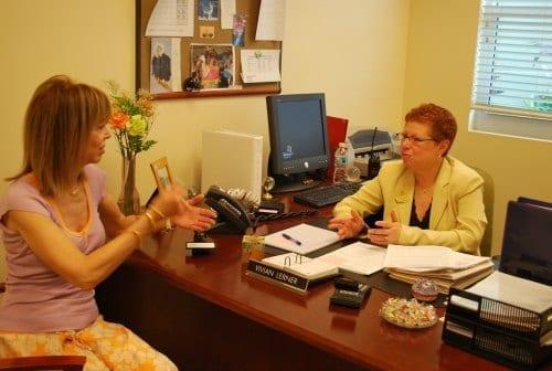Two woman talking inside of an office