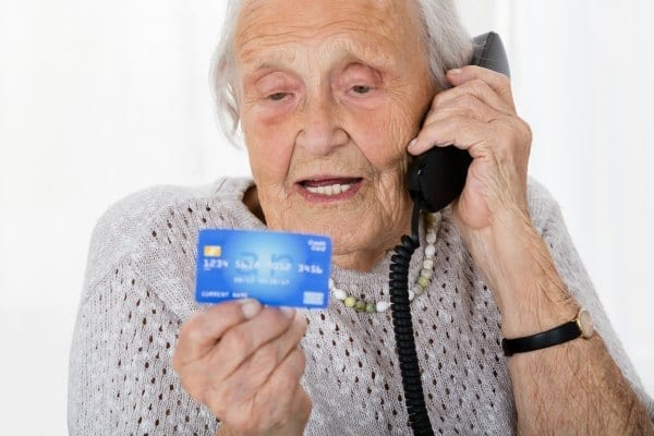 An elderly woman holding a credit card while on the phone