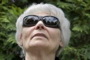 An elderly woman wearing black sunglasses