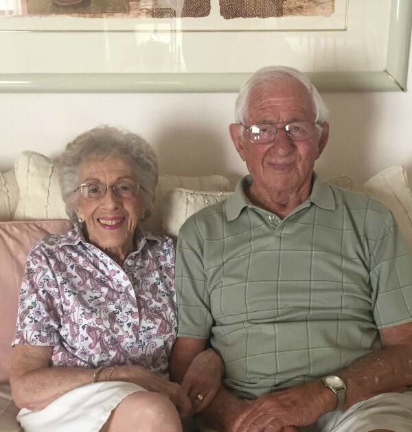 An elderly couple sitting together on a couch
