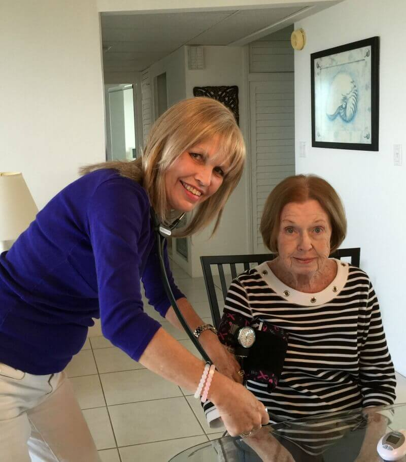 Caregiver taking the blood pressure of elderly patient