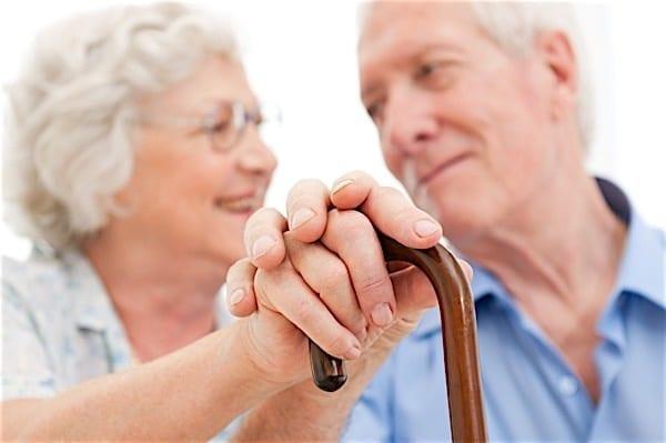 Elderly couple both holding cane