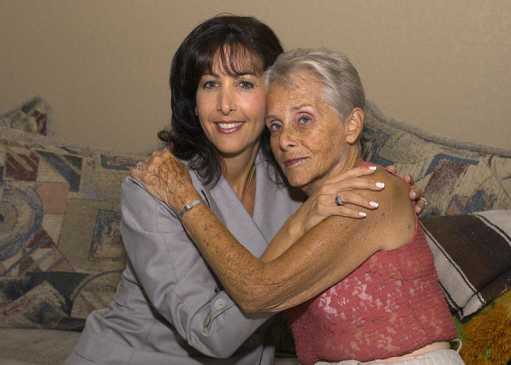 Two women hugging each other on couch