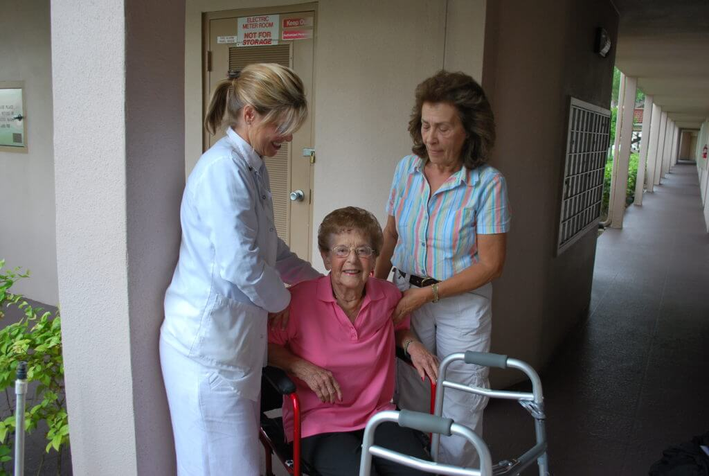 Two women helping an elderly woman into her wheelchair