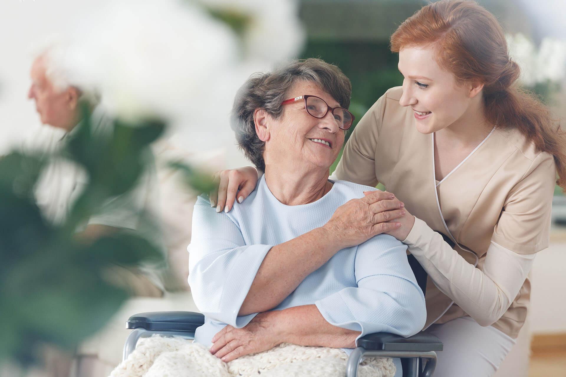 Senior citizen in wheelchair and caregiver
