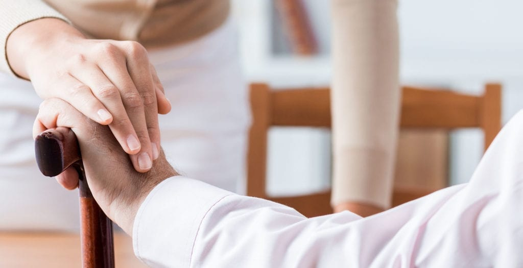 caregiver putting hand over seniors hand