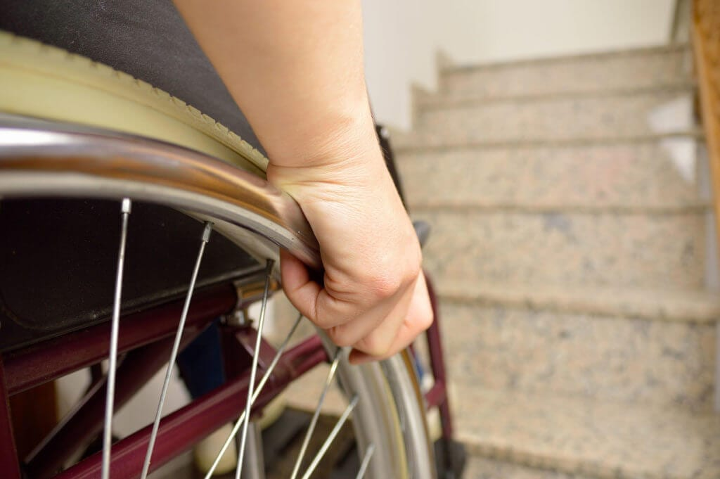 young disabled man in wheelchair in front of stairs at home