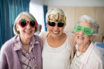 Older woman at assisted living facility smiling with fun glasses