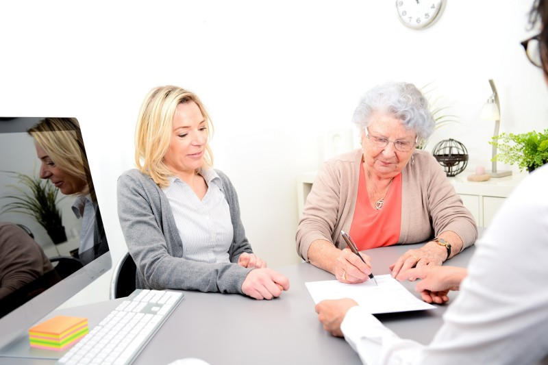 Woman signing paperwork with doctor