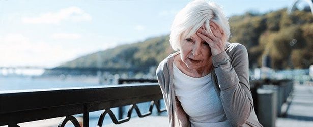 old women touching her head because of pain